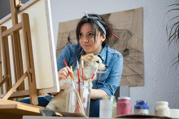 Little dog enjoys with female painter
