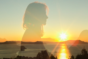 double exposure warm profile portrait of young woman wearing sweatshirt, sea , hills and sunrise on the background