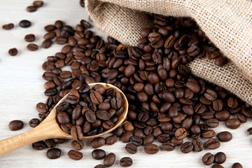Wall Mural - wooden spoon and roasted coffee beans and coffee bag close up