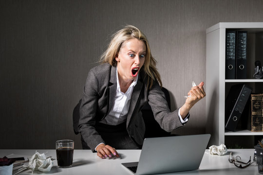 Woman angry at her laptop computer at work