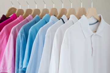 Man's shirts hanging on rack in row