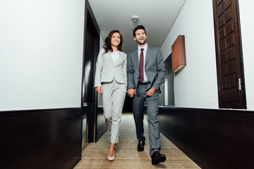 cheerful businessman and happy businesswoman in formal wear holding hands and walking in hotel corridor