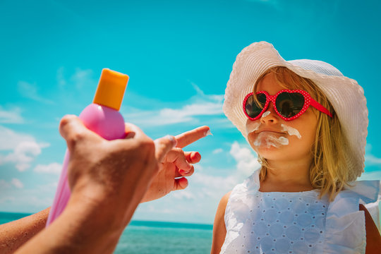 sun protection - mom put suncream on little girl face at beach
