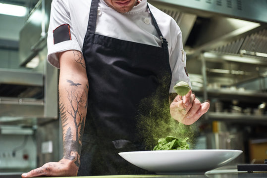 Slow motion. Cropped image of chef's hands with tattoos adding spices in salad while standing in a restaurant kitchen.