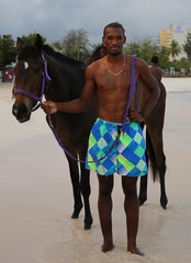 A stable boy from the Garrison Savannah racecourse poses for a photograph before he washes his horse in the sea at Pebbles Beach near Bridgetown