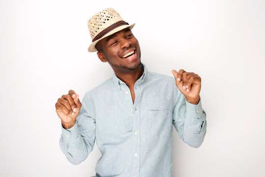 happy african american man with hat dancing against isolated white background