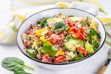 Quinoa salad with fresh vegetables on white.