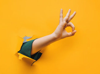 Hand OK sign. The teenage hand came out into the hole of yellow paper and shows symbol of Okay. Copy space, fine. Wall mural