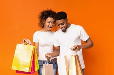 Happy black couple looking into shopping bags