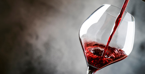 In de dag Wijn French dry red wine, pours into glass, gray background, banner, selective focus