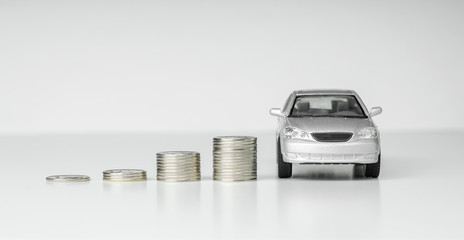 concept, height, stacks of silver coins next to a toy car on a white background.