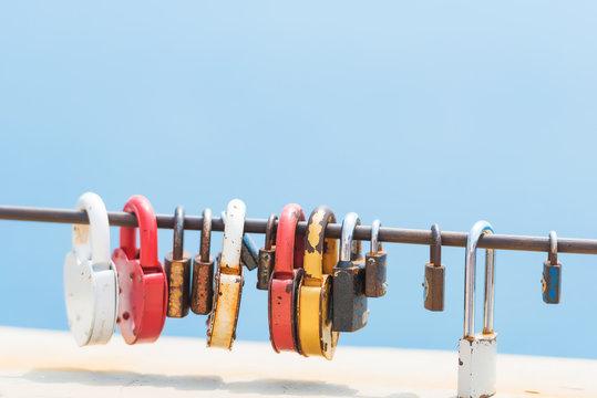Colored locks on the bridge. Rest in Crimea. Metal handrail on which the locks hang. Black Sea.