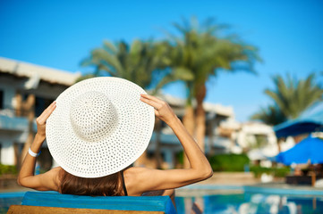 Woman in big white hat lying on a lounger near the swimming pool at the hotel, concept summer time to travel Wall mural
