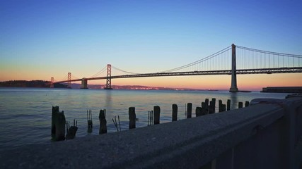 Fototapete - Motion controlled dolly shot with dolly up-left motion of the Bay Bridge at sunset in San Francisco, California