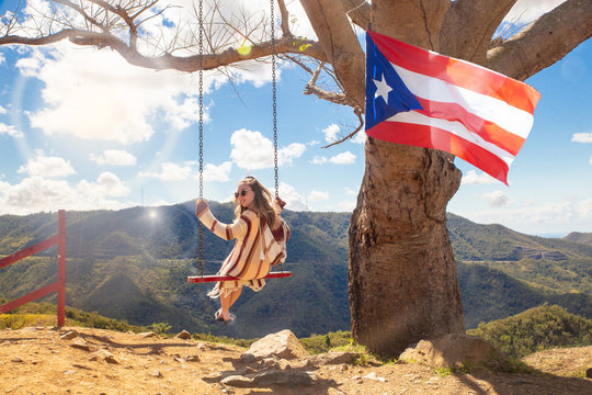 Happy girl swinging from tree over mountain landscape at Curva Del Arbol in Cayey Puerto Rico