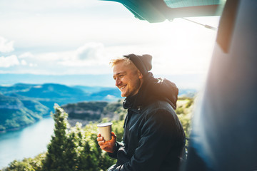 hipster tourist hold in hands mug of hot drink, lonely guy smile enjoy sun flare mountain in auto, happy traveler drink cup of tea on nature, vacation weekend concept on panoramic landscape Wall mural