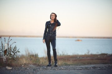 beautiful sexy girl with long hair in a leather jacket and leather pants standing on the beach at sunset