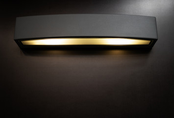 Black metal angular wall lamp with yellow light on with copy space