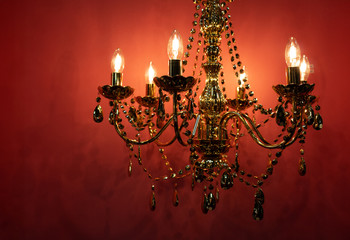 Luster as old fashion ceiling lamp decorated with metallic crystals and chains with overall golden look