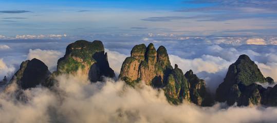 Chinese Karst Mountains above the clouds, steep cliffs covered in exotic trees. Dayao Mountain range near Jinxiu City, Guangxi Province China. Shengtang Mountain, Shengtangshan. Hiking and Travel