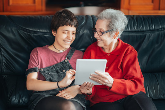 Granddaughter teaches her grandmother how to use a tablet