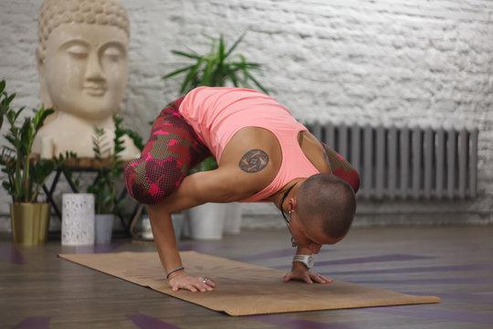 tanned skinhead woman with ethnic tattoos in yoga crane pose - bakasana