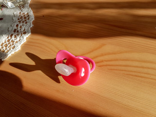 pacifier red on wooden table