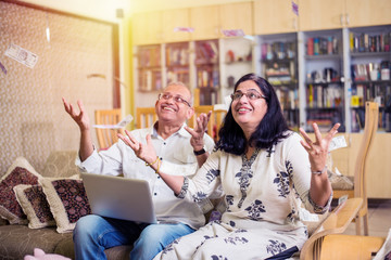 Happy Senior Indian/asian couple having won lottery or investment earning in form of Money/paper currency falling from sky / raining concept