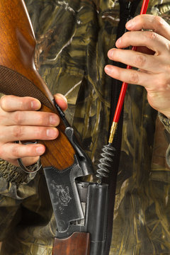 shooter cleans the barrels of a shotgun