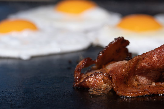 Closeup image of a cooking bacon on a barbecue at a school fundraiser on election day in Australia