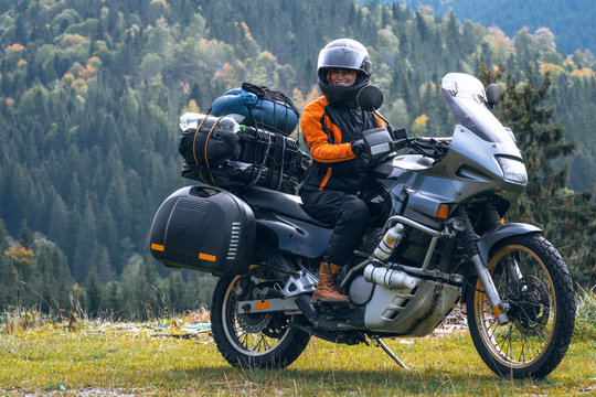 Woman biker with big adventure motorbike, motorcyclists vacation, world traveler, long road trip on two wheels. autumn day. Mountains on background. Romania