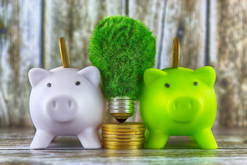 Piggy banks, green eco light bulb with grass and golden coins on wooden background. Renewable energy concept. Electricity prices, energy saving in the household.