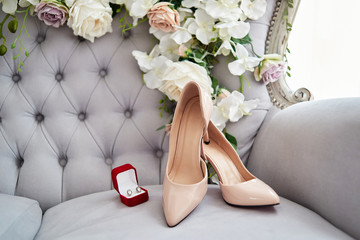 Beautiful beige bride shoes on high heels and earings on lavender chesterfield chair with flowers, copy space. Luxury bridal accessories and jewelry. Wedding morning preparations Wall mural