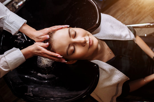 Gorgeous cute young woman enjoying head massage while professional hairdresser applying shampoo her hair. Close up of hairdresser's hands washing hair to the client.