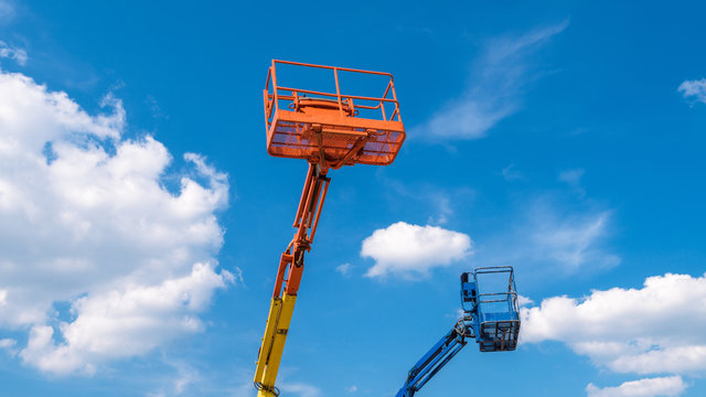 Cherry pickers on blue sky background. Boom with lift buckets of heavy machinery. Platforms of the telescopic construction lifts in summer.