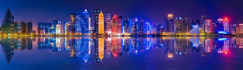 Banner of capital city of Qatar by night. Doha West Bay skyline mirroring in Doha Bay. Panorama of glassed skyscrapers of Doha, Qatar, Middle East, Arabian Peninsula in Persian Gulf. Night urban scene