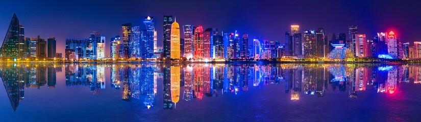 Banner of capital city of Qatar by night. Doha West Bay skyline mirroring in Doha Bay. Panorama of glassed skyscrapers of Doha, Qatar, Middle East, Arabian Peninsula in Persian Gulf. Night urban scene Fototapete