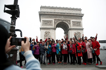 """Chinese tourists pose for photos in front of the Arc de Triomphe on the Champs-Elysees avenue during the Act XIX (the 19th consecutive national protest on a Saturday) of the """"yellow vests"""" movement in Paris"""