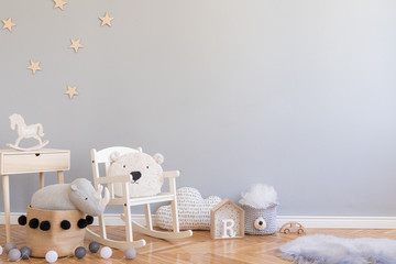 Stylish scandinavian newborn baby room with wooden toys, teddy bear on children's chair, natural basket with rhino. Modern interior with grey background walls, wooden parquet and stars pattern.