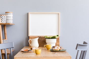 Stylish and modern interior of kitchen space with small wooden table with mock up photo frame, plants, design cups, furnitures and tasty dessert. Scandinavian room decor with kitchen accessories.