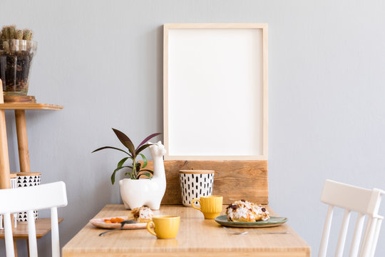 Stylish and sunny interior of kitchen space with small wooden table with mock up photo frame, design cups and tasty dessert. Scandinavian room decor with kitchen accessories, cacti and plants.