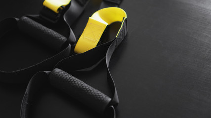 Black and yellow strap functional training equipment on grey background. Sport accessories. Fitness and Gym workout items for Healthy. Banner TRX