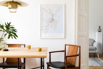 Stylish and eclectic dining room interior with mock up poster map, sharing table design chairs, gold pedant lamp and elegant sofa in second space. White walls, wooden parquet. Tropical leafs in vase. Wall mural
