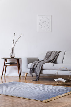 Stylish scandi interior of home space with design grey sofa and retro small table. Living room with design accessories and mock up poster frame. Elegant decor. Brown wooden parquet with modern carpet.