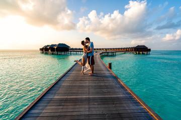 A couple enjoying a sunrise in the Maldives.