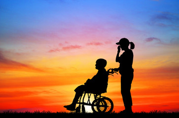 silhouette Daughter to care a wheelchair mother to walk on
