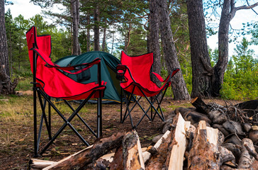 View of tourist camp with red folding chairs, camping tent and firewood near the bonfire in the forest.