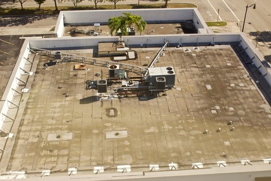 Building roof top, aerial view. Building roof top, from higher building adjacent, showing air conditioning units and electrical raceway