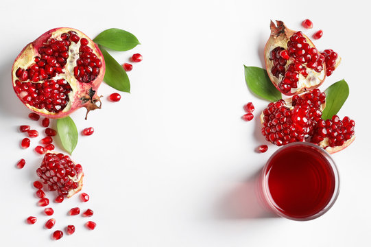 Glass of pomegranate juice and fresh fruits on white background, top view with space for text