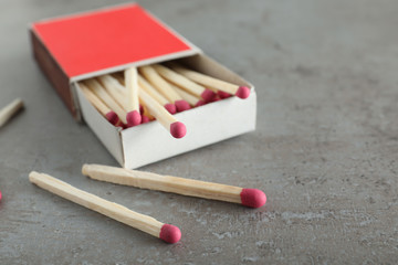 Open box and scattered matches on grey background, space for text